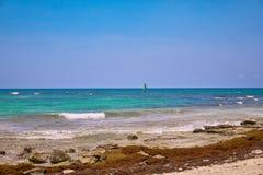 海滩热带视图 游人乘驾有降伞的帆伞运动小船 航行在波浪的游艇风帆 绿松石水  免版税库存图片