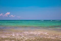 海滩热带视图 游人乘驾有降伞的帆伞运动小船 航行在波浪的游艇风帆 绿松石水  免版税库存照片