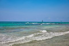 海滩热带视图 游人乘驾有降伞的帆伞运动小船 航行在波浪的游艇风帆 绿松石水  库存照片