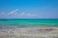 海滩热带视图 游人乘驾有降伞的帆伞运动小船 航行在波浪的游艇风帆 绿松石水  图库摄影