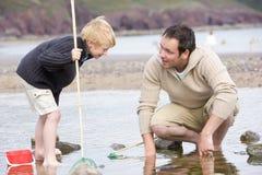 海滩父亲捕鱼儿子 库存照片