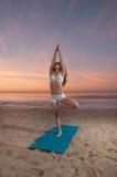 海滩瑜伽妇女 免版税库存照片