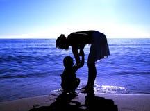 海滩男孩帮助的妈妈 免版税库存照片