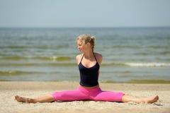 海滩白肤金发的女性锻炼 库存照片