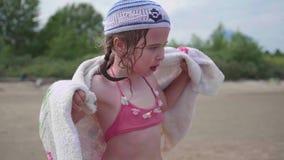 海滩的一个女孩抹身体与毛巾在沐浴以后 暑假,由海的休息 股票录像
