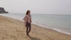 海滩的一名白肤金发的妇女由海 股票视频