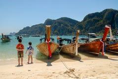 海滩的两个男孩与长尾巴小船 免版税库存照片