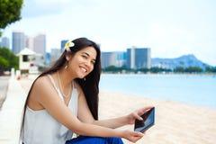 海滩的两种人种的青少年的女孩使用片剂计算机,威基基, Hono 免版税库存照片