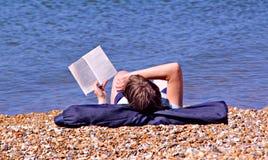 海滩的书痴 库存图片