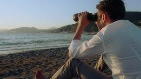 海滩的人与双筒望远镜 股票录像