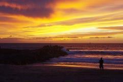 海滩的人享受日落的 免版税库存照片
