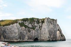 海滩的人们在白垩峭壁附近在Etretat 库存照片