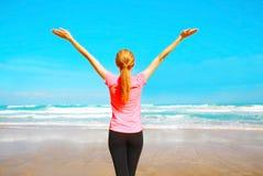 海滩的健身愉快的妇女在海附近 库存照片
