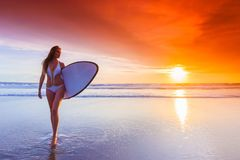 海滩的冲浪者妇女在日落 免版税图库摄影