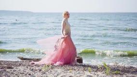 海滩的可爱的夫人享用风,拿着有她的手指的轻的薄纱羽毛,梦想,听声音的 股票视频