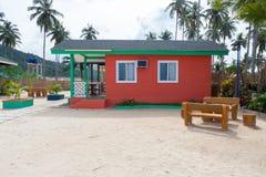 海滩的多彩多姿的木房子与棕榈和白色沙子 有大窗口的东方建筑学假日房子 免版税库存照片