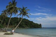 海滩的女孩反对海和棕榈树的背景 免版税库存照片