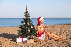 海滩的女孩坐圣诞树手段鸡尾酒 库存照片