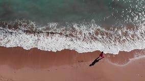 海滩的女孩 红色礼服的妇女走在沙滩的 步行沿着向下海滩的年轻可爱的女孩 沙滩鸟瞰图  影视素材