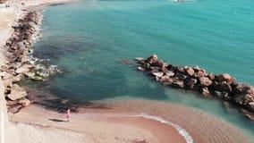 海滩的女孩 红色礼服的年轻女人走沿岩石石头的 沙滩的可爱的女孩 红色dre的逗人喜爱的白种人夫人 股票录像