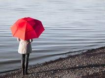 海滩的妇女与一把红色伞 免版税库存照片