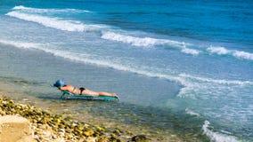 海滩的妇女在躺椅,在水中间,在海滨和海洋,有蓝色帽子和海的与 免版税库存图片