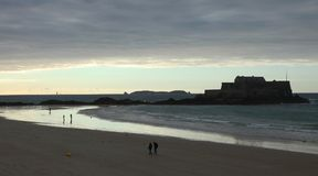 海滩的孤独的人在日落和看法对盛大的堡垒在圣马洛湾 库存照片