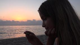 海滩的孩子,孩子使用在日落的岸的,观看的女孩学习小卵石 股票视频
