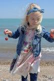 海滩的小女孩在一个有风春日 免版税库存图片