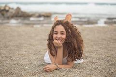 海滩的年轻卷曲女性 库存图片