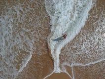 海滩的愉快的女孩在海浪形成上面 库存图片