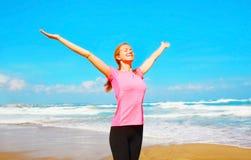 海滩的愉快的微笑的妇女在海附近 免版税库存图片