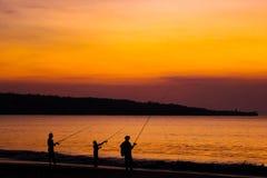 海滩的渔夫在巴厘岛海岛上日落的 库存图片