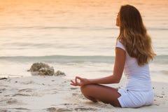 海滩的瑜伽妇女在日落 免版税库存照片