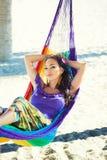 海滩的相当惊奇的快乐的女孩,微笑在吊床在反对棕榈树背景,生活方式,被晒黑 库存照片