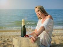 海滩的美丽的妇女与一个瓶冷的香槟和草莓 免版税库存照片