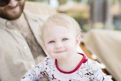 海滩的美丽的愉快的传神白肤金发的女孩小孩与她的父亲 免版税库存图片