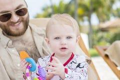 海滩的美丽的愉快的传神白肤金发的女孩小孩与她的父亲 库存照片