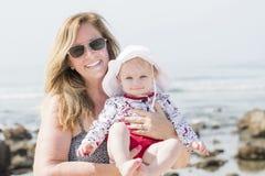 海滩的美丽的愉快的传神白肤金发的女孩小孩与她的祖母 免版税图库摄影