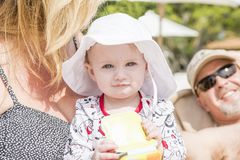 海滩的美丽的愉快的传神白肤金发的女孩小孩与她的祖父母 免版税库存图片