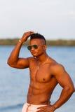 海滩的肌肉年轻运动性感的人与在内衣的赤裸躯干 热的黑人美丽的人,与徘徊的健身模型 免版税库存图片