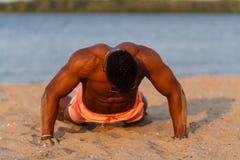 海滩的肌肉年轻运动性感的人与在内衣的赤裸躯干 热的黑人美丽的人,健身模型 免版税库存图片