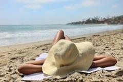 海滩相当晒日光浴的年轻人 免版税库存照片