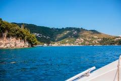 海滩看法与岩石峭壁和白色房子,旅馆的在希腊海岛 corfu 欧洲旅行 小船海洋和平的海景热带越南视图 海景 图库摄影
