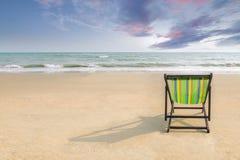 海滩睡椅和阴影在白色沙子靠岸与日落光 免版税库存照片