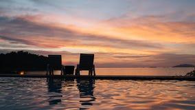 海滩睡椅手表日落在晚上在泰国的夏天 免版税库存图片