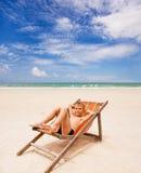 海滩睡椅的滑稽的男孩在海滩 免版税库存照片