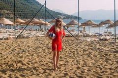 海滩礼服的微笑的妇女有在沙子的球身分的,假期 免版税库存图片