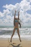 海滩美丽的女孩跳的年轻人 免版税库存图片