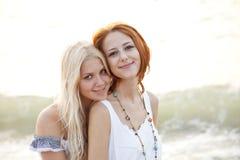 海滩美丽的女朋友二个年轻人 免版税库存照片
